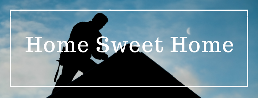 A silhouette of a roofing professional repairing the asphalt shingles on top of rooftop.